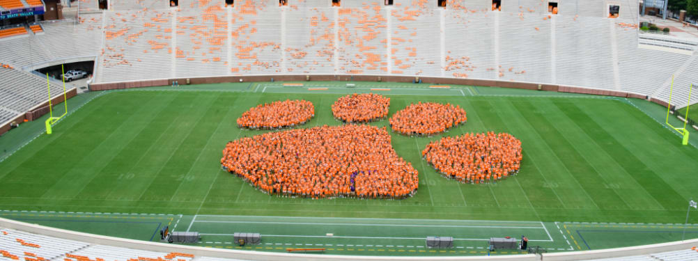 Clemson students in orange t-shirts stand in the shape of a tiger paw on the football field in Death Valley.