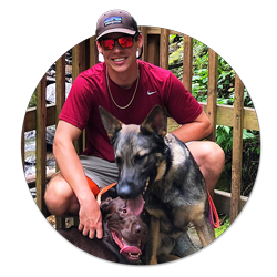 Student Ryan King, wearing a gray Patagonia hat and a red T-shirt, poses in front of a waterfall with two dogs, a German shepherd and a Labrador retriever