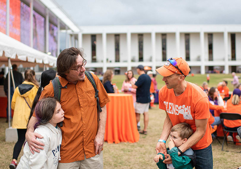Clemson faculty and their children interact at a gathering behind Cooper Library.
