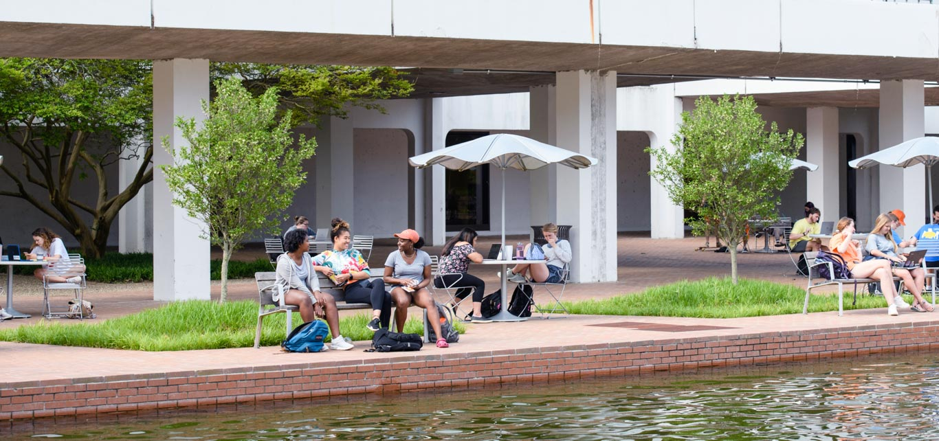 Clemson students sit at tables underneath library bridge beside the reflection pond.