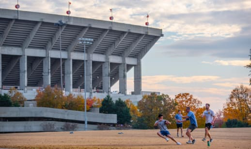 Four male Clemson students play touch football on an intramural field beside Memorial Stadium.