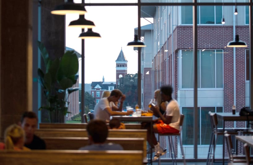 Clemson students sit together in a dining hall in Douthit Hills as the sun sets and highlights Tillman Hall.