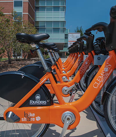 Orange bike-share bikes stand in a row outside Clemson's student center.
