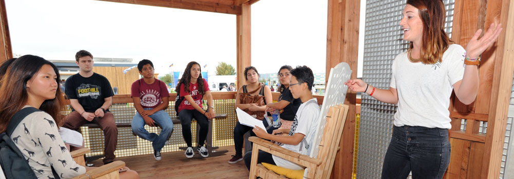 "Allie Beck speaks to students on the porch of ""Indigo Pine"" - Clemson University's design submisison for the U.S. Department of Energy Solar Decathlon.Orange County Great Park, Irvine, California, Oct. 15, 2016"