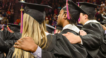 Clemson students embrace during the singing of the alma mater during graduation