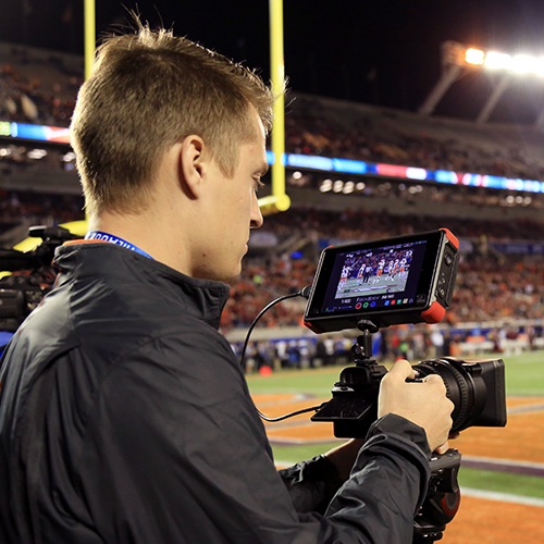 Max working a camera at a Clemson Football game.