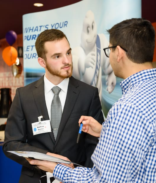 Male Clemson engineering student in professional attire speaks with Michelin representative at the career fair.