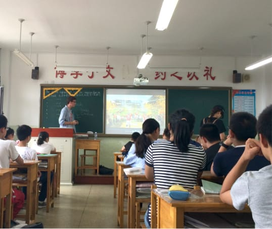 Male Clemson student presents to a class of children in Japan.