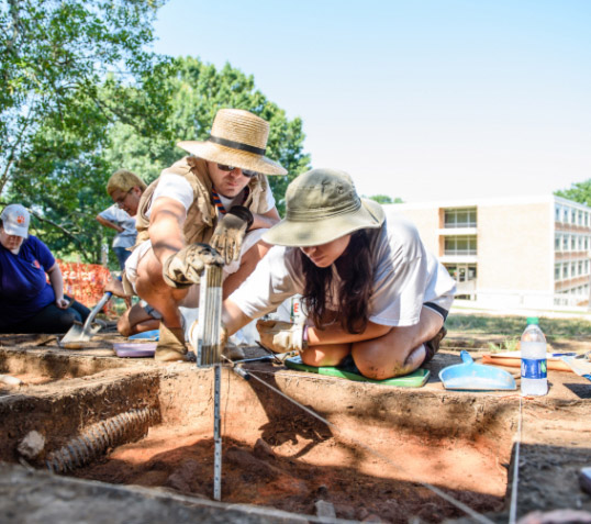 Two Clemson students in wide-brimmed hats measure the depth of a dig they're conducting on campus in front of the Shoeboxes.