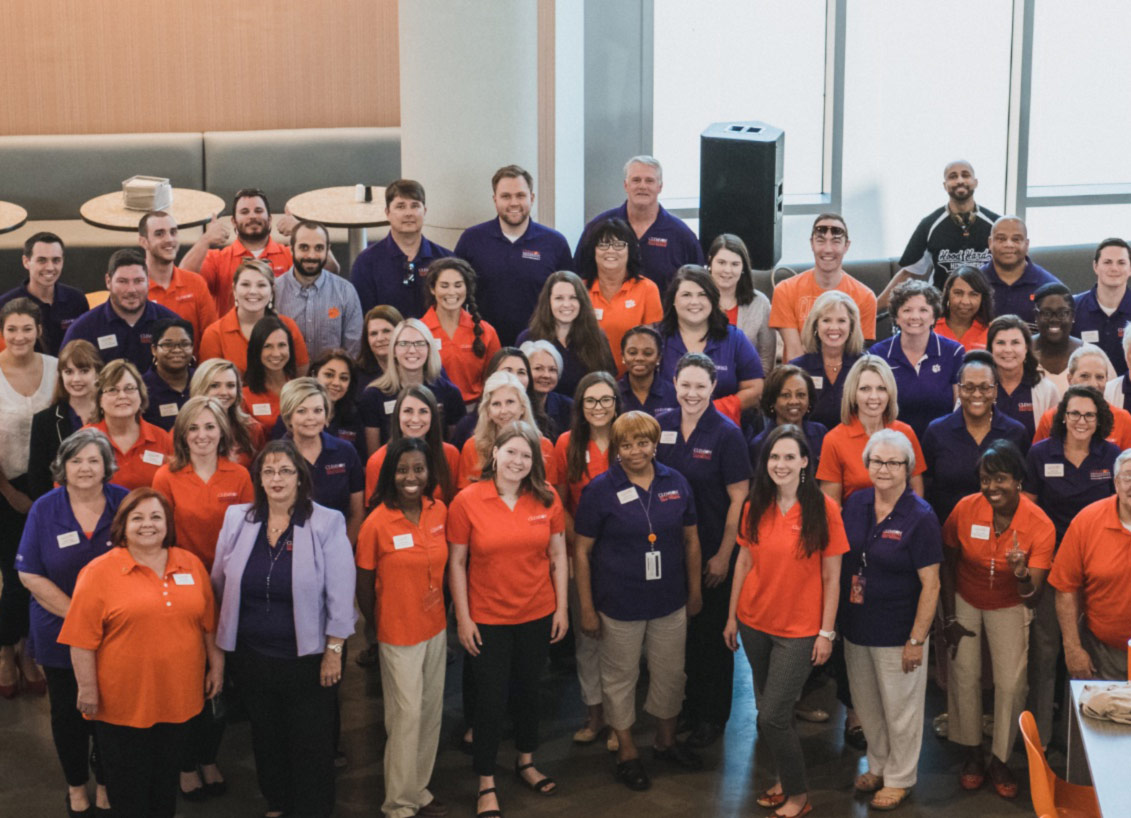 A group of Clemson employees wearing orange and purple pose together, smiling.