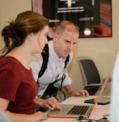 A male Clemson employee assists a female student with something on her computer.