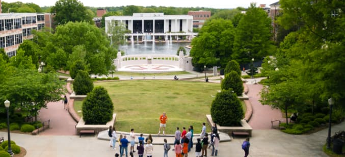 An aerial view of a tour guide addressing his group with the ampitheater, reflection pond and Cooper Library behind him.