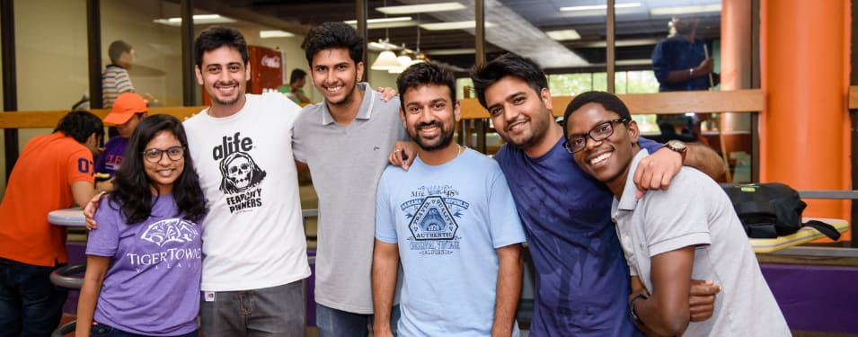 A group of international students with arms around each other smile at the camera.