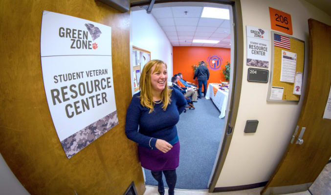 A female employee smiles, opening the door to the student veteran resource center.