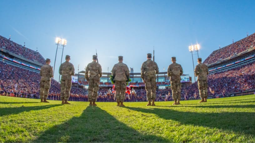 ROTC cadets stand in formation on the football field during a pregame ceremony.
