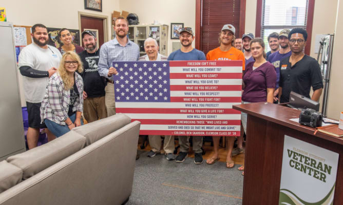A group of staff and students stand behind a flag and smile in the student veteran resource center.