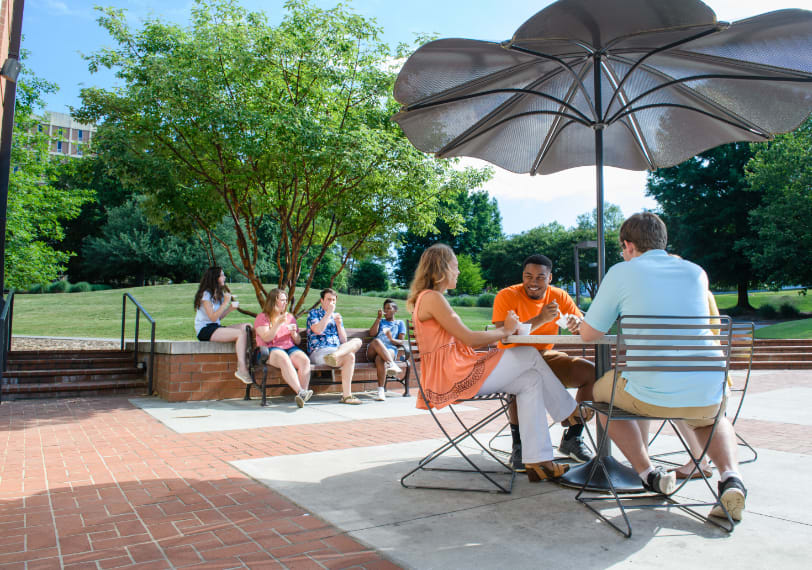 Small groups of students sit together and enjoy ice cream outside of Hendrix Student Center.