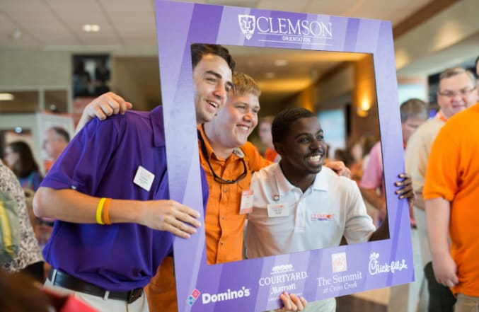 Two male orientation ambassadors pose with one of the new Clemson students in their group during Orientation.