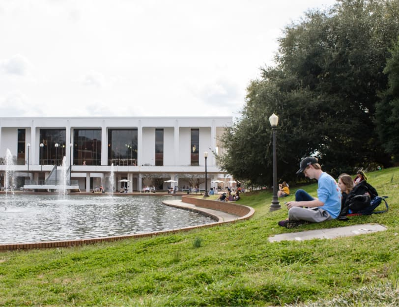 Clemson students study while sitting in the grass beside the reflection pond and Cooper Library.