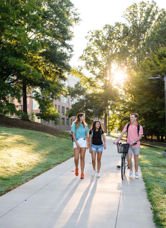Three students walk beside Douthit Hills as the sun shines through the trees.