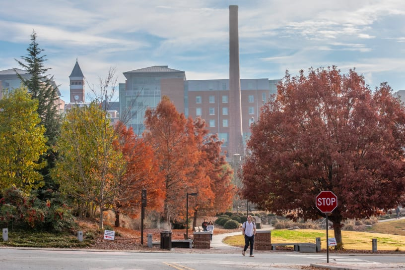 A student walks across the intersection between the Scroll of Honor Memorial and Death Valley amid bright fall foliage.