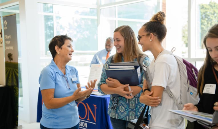 Female students talk with a middle-aged female employee during a job fair in Littlejohn Coliseum.