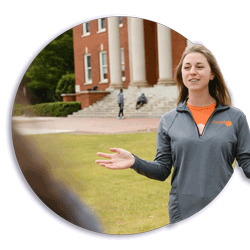 Catherine Chapman gives a tour of Clemson University to prospective students. In the background is Sikes Hall.