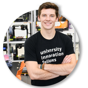"Gabriel Herman, wearing a black T-shirt that reads ""university innovation fellows"" in white type, poses for a photo in the Clemson University Makerspace."