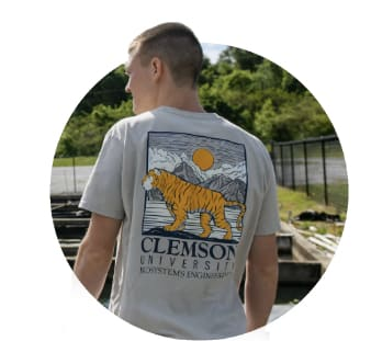 Male student stands in the sun, showing a Clemson design on the back of his t-shirt.