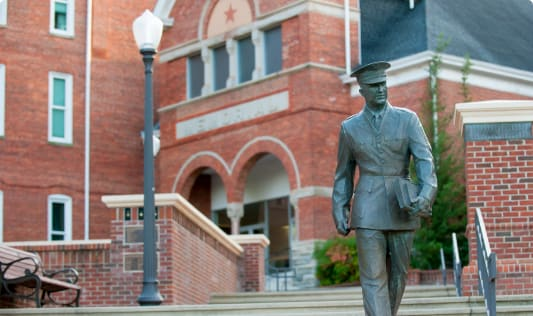 A statue shows a Clemson cadet holding a book striding from campus toward Bowman Field.