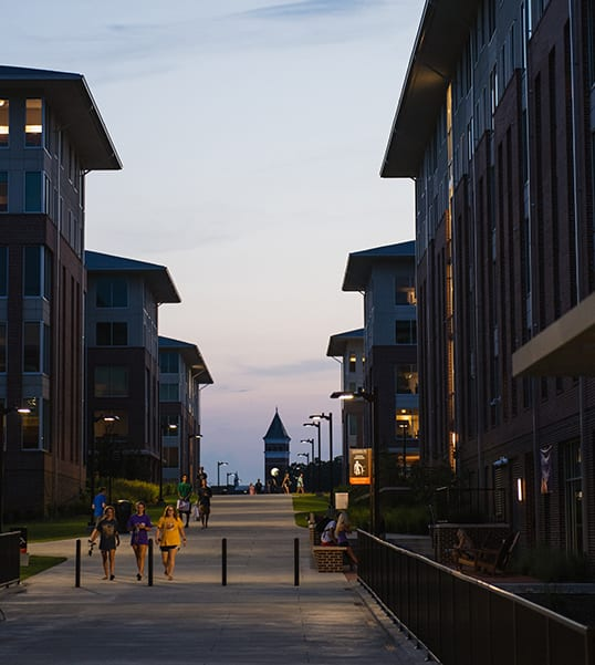 Clemson students walk between the buildings of Douthit Hills at dusk with Tillman Hall in the background.