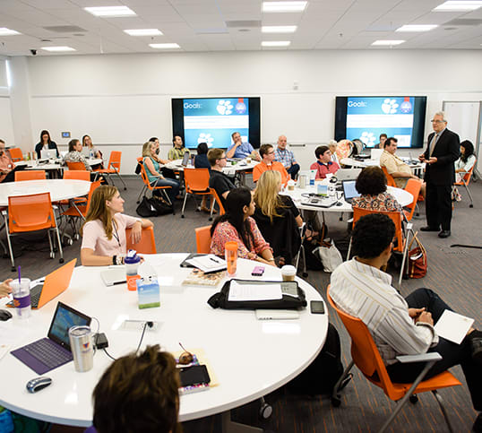 Clemson faculty and staff sit at round tables in the Watt Innovation Center during a training session.