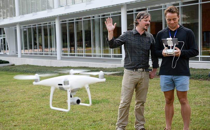Clemson professor explains a concept as a drone hovers nearby.