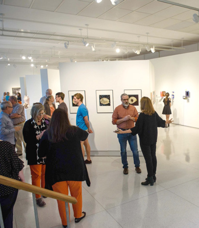 A group of students and faculty attend a gallery showing in Lee Hall