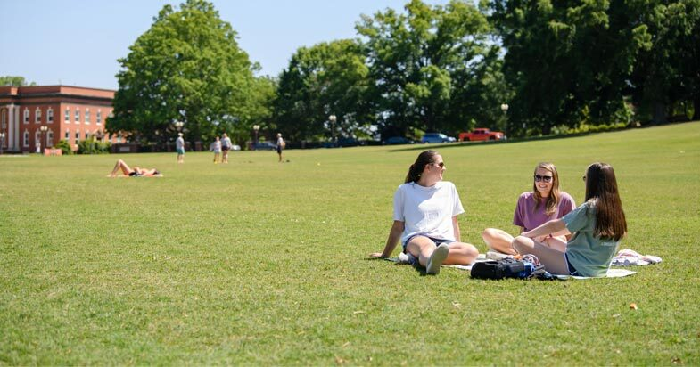 Three female undergraduate students smile and talk, sitting together in the sunshine on Bowman Field.