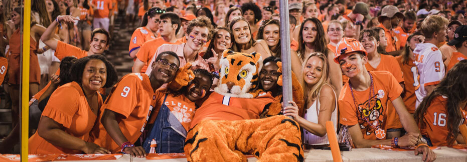 The Tiger mascot reclines and poses with orange-clad students on the front row of Death Valley during a night football game.
