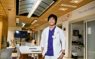 Nam stands, smiling with hands in his pockets in a brightly lit nursing simulation lab wearing white and purple Clemson scrubs.