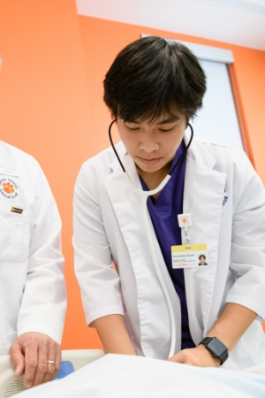 Nam takes the pulse of a human simulator in the lab by his professor, using a stethoscope, wearing purple and white scrubs.