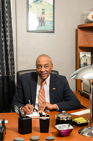 Roy Jones looks at the camera while writing a letter at his desk, wearing a black suit and orange tie.