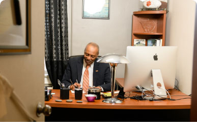Roy Jones writes with a pen on a wooden desk in his office while wearing a black suit and orange tie.