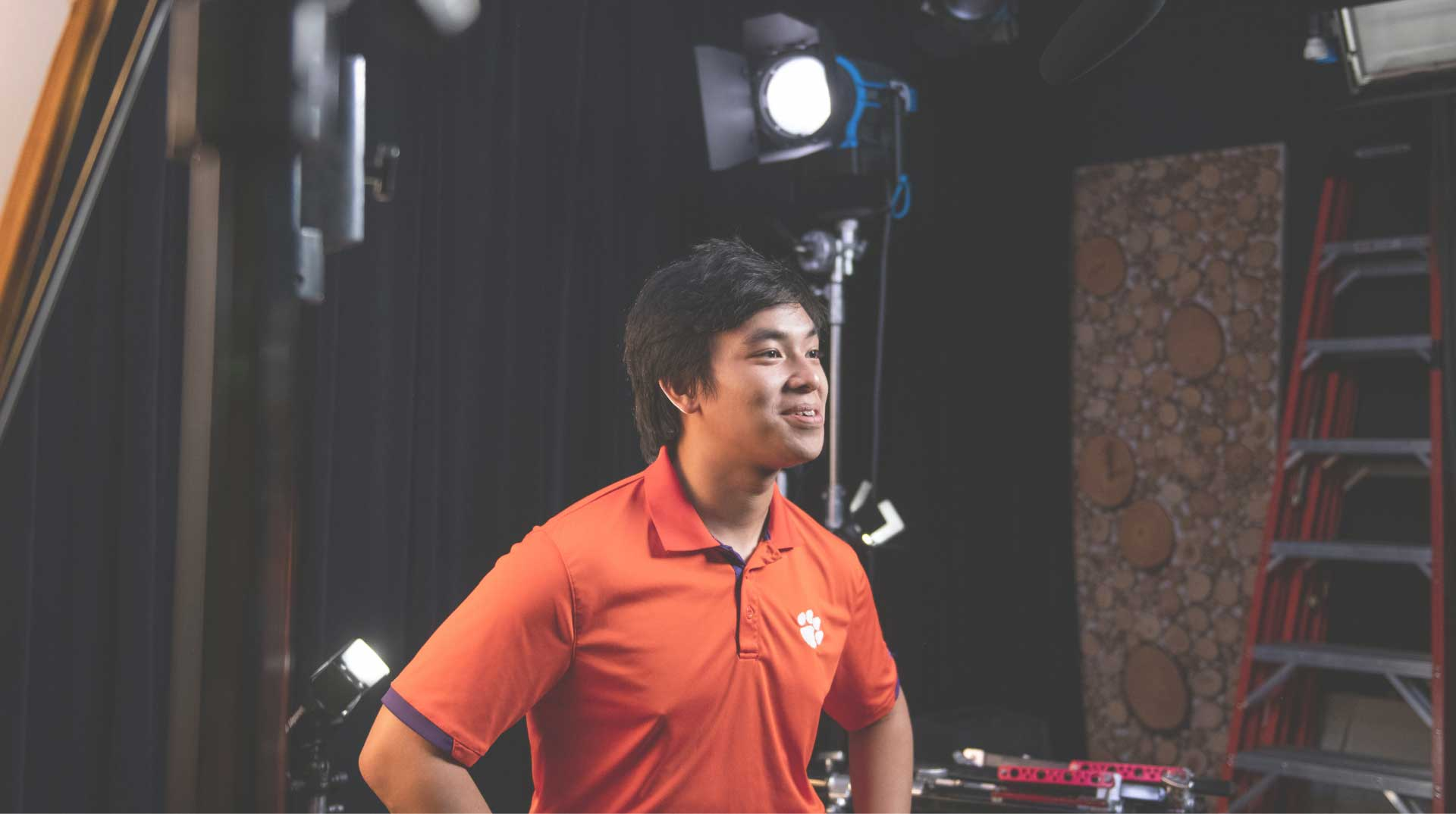 Nam sits in a backstage video area wearing an orange Clemson polo and talking. 'Watch Nam's Story' and the play symbol hover beside him.