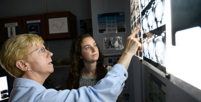 Faculty advisor and undergraduate student examine Xrays together.