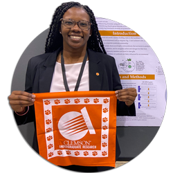 "Student Erin Walker presents her research at a conference and smiles while holding an orange cloth that reads, ""Clemson Undergraduate Research."""