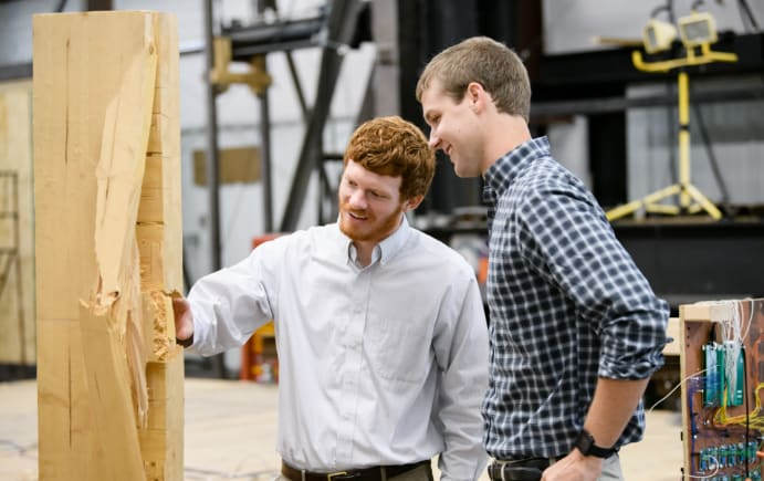 Graduate student Graham Montgomery and undergraduate assistant examine split wood while conducting mass timber research.