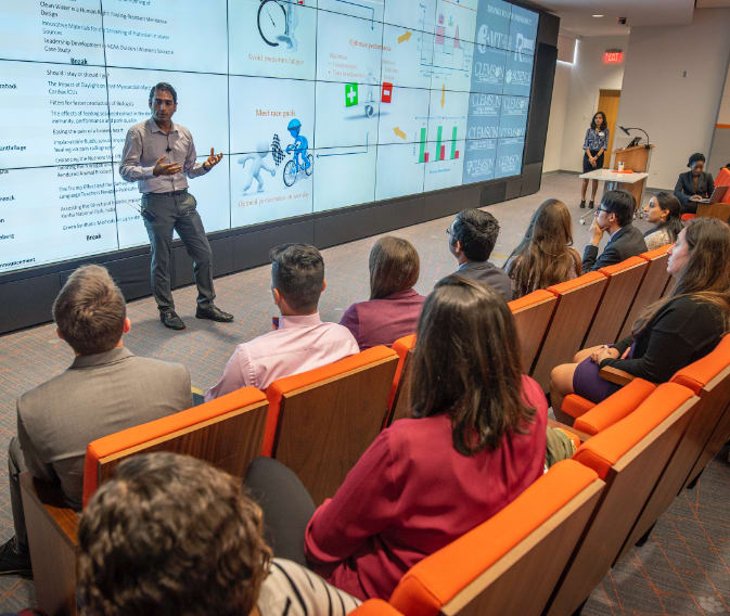 Man presents data to group in Erwin Center for Brand Communication.