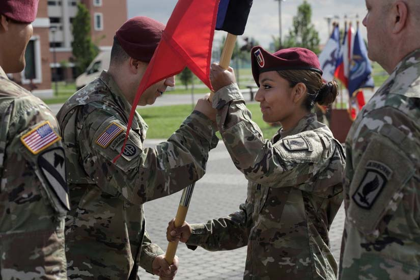 Doctoral student Maira Patino, middle right, wearing a U.S. Army uniform, is handed a flag by a man who is also wearing a U.S. Army uniform.