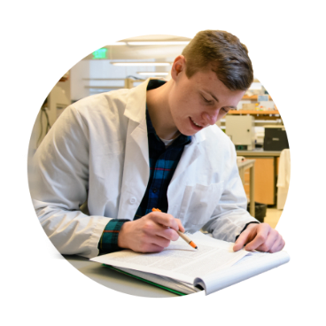 Biochemistry student Nate Matzko writes in a notepad in his lab.