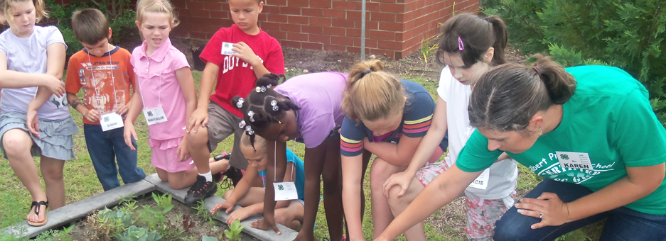 kids gardening with adult volunteer