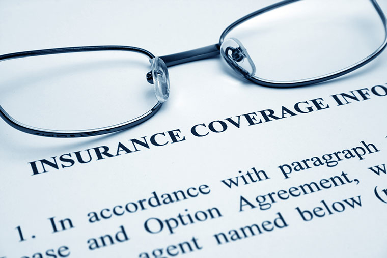 glasses placed on top of insurace coverage document