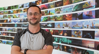 Marc Bryant poses in front of Disney animation storyboards